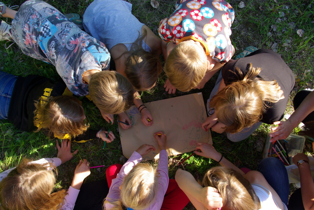 Leiriläiset piirtävät ulkona nurmikolla istuen.